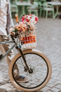 A man walking with his bike & flowers to a his civil wedding in zurich